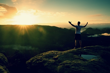 Runner on the peak. Man in his target gesture triumph with hands in the air. Crazy man in black pants and white t-shirt, Stock Photo