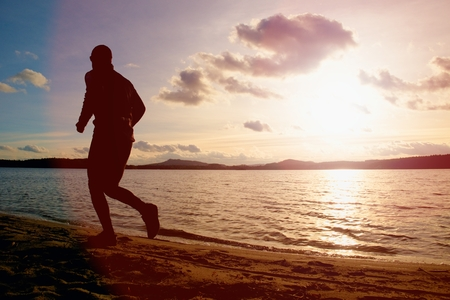 Silhouette of sport active man running and exercising on the beach water mountain and sunset cloudy sky background. Reklamní fotografie