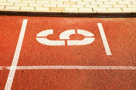 number six: Number six. White athletic track number on red rubber racetrack, texture of racetracks in small stadium