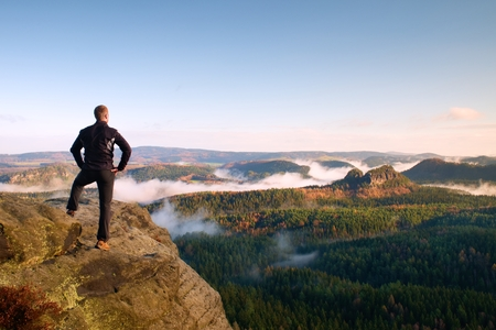 empires: Hiker stand on cliff of sandstone empires park and watching over the misty and foggy morning valley to Sun