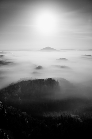 increased: Full moon night with sunrise in a beautiful mountain of Bohemian-Saxony Switzerland. Sandstone peaks and hills increased from foggy background