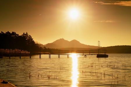 stronghold: Colorful autumn sunrise at coastal, abandoned wharf. Island with stronghold at horizon.