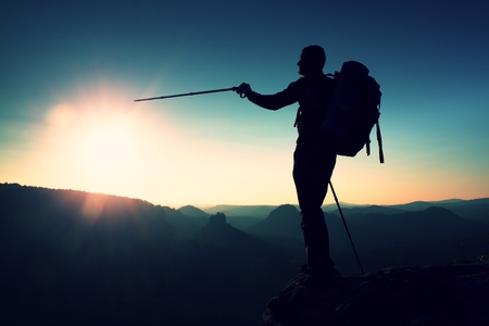 tall man: Sharp silhouette of a tall man on the top of the mountain with sun in the frame