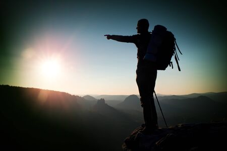 tourist guide: Sunrise with inversion.Cliff above deep autumn valley with tourist guide on the top. Hiker, who is watching this breathtaking  beautiful scenery