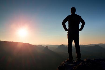 iluminado a contraluz: Silueta de joven hombre seguro y poderoso de pie con las manos en caderas, Abierto Día de Sun con Espacio en blanco