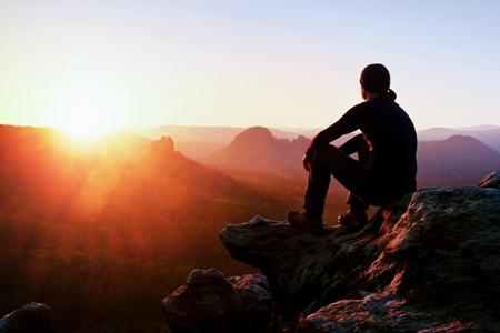 gente sentada: turista adulto con pantalones negro, chaqueta y gorra oscura se sienta en el borde del precipicio y mirando abajo en Misty valle montañoso