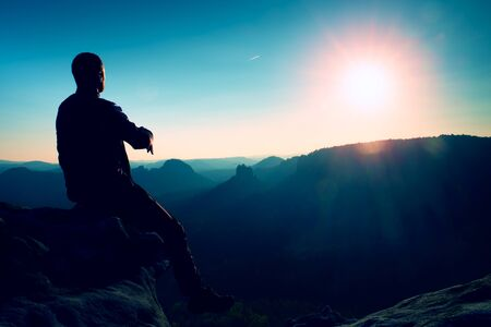 blue sky thinking: Handsome young man sitting on the rock and enjoying view into misty rocky mountains.