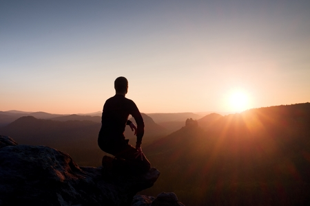 edge of cliff: Young man in black sportswear sit on cliff edge and look into red Sun at horizon over misty valley
