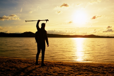 Tall hiker in dark sportswear with poles and sporty backpack on beach enjoy sunset at horizon with blue sky with clouds. Magic autumn day.