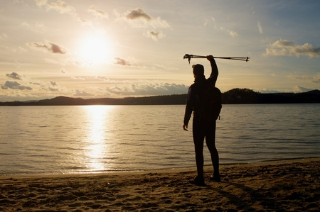 end of the trail: Tall hiker in dark sportswear with poles and sporty backpack on beach enjoy sunset at horizon with blue sky with clouds. Magic autumn day.