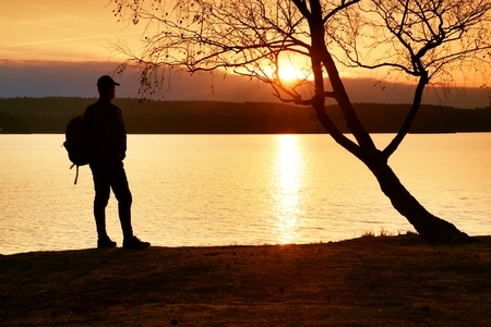 end of the trail: Happy man with hand in the air. Tall hiker in dark sportswear with sporty backpack stands on beach enjoy sunset at horizon with pink orange sky with clouds. Magic autumn day.