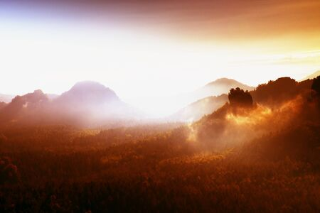 foggy hill: Red filter photo. Red daybreak. Misty daybreak in a beautiful hills. Peaks of hills are sticking out from foggy background, the fog with red and orange due to Suns rays. Stock Photo