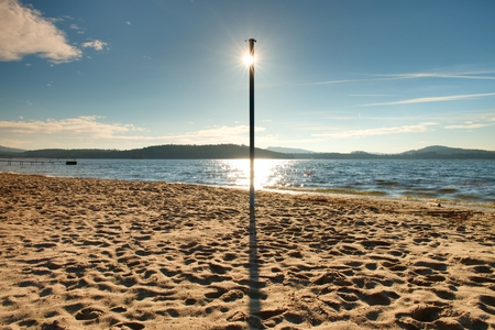 sunup: Sun hidden behind blue pole on sandy beach at sea. Forest hill on island in background. Vivid colors
