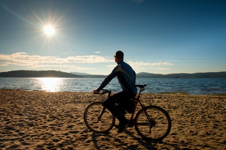 tourist resort: Young man cyclist sit on bike,  blue sky and sunset background on beach. End of season at lake and popular tourist resort..
