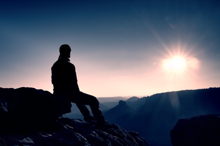 strong: Handsome young man sitting on the rock and enjoying view into misty rocky mountains.