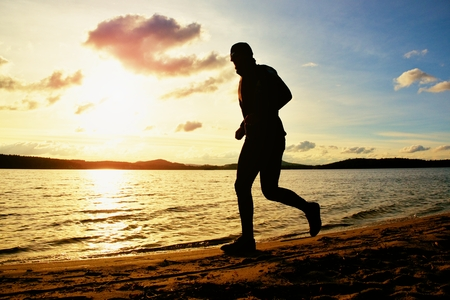 tall man: Tall man with sunglass and dark cap is  running on the beach at sunset