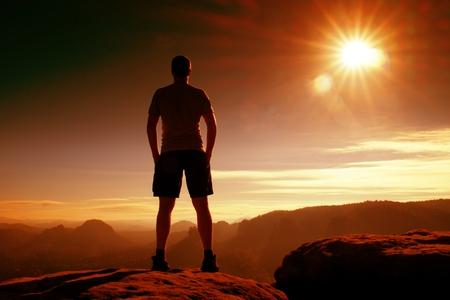pantalones abajo: foto filtro rojo. turismo delgada en pantalones en el acantilado de roca imperio está mirando hacia abajo al valle de niebla por la mañana. Sun caliente por encima.