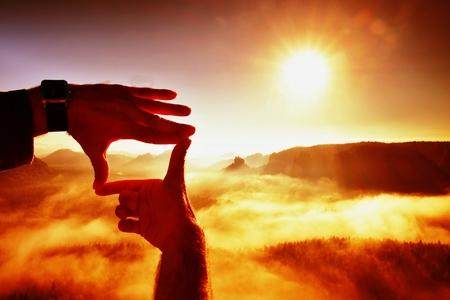 planeaci�n: Cerca de las manos que hacen gesto del marco. valle brumoso azul abajo pico rocoso. Soleado de primavera del amanecer en las monta�as. Foto de archivo