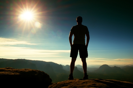 mornings: Hiker Alone in black pants stand on rock empire and watching over the misty and foggy mornings Sun Valley Beautiful moment the miracle of nature Stock Photo