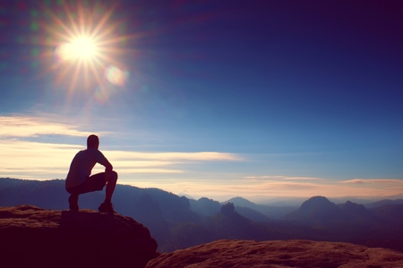 Slim tourist on sharp peak of rock watch over misty and foggy morning valley to Sun. Dreamy morning nature. Stock Photo