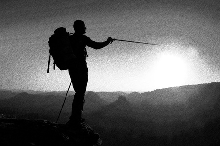tall man: Black and white dashed retro sketch. Sharp silhouette of a tall man on the top of the mountain with sun in the frame