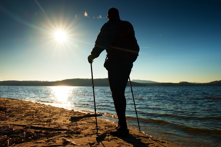 end of the trail: Hiker in dark sportswear with poles and sporty backpack on beach enjoy magic autumn day. Stock Photo