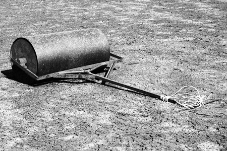 barrel tile: Black and white dashed retro sketch. Old rusty iron barrel for maintenance of neglect tennis court. Old dry red crushed bricks surface on outdoor tennis ground. Stock Photo