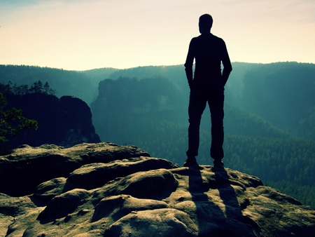 empires: Tall Hiker stand on the peak of sandstone rock in rock empires park and watching over the misty and foggy mornings Sun Valley Beautiful moment the miracle of nature Stock Photo