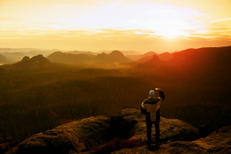Man takes photos with smart phone on peak of rock empire. Dreamy fogy landscape, spring orange pink misty sunrise in a beautiful valley of Saxony Switzerland park.