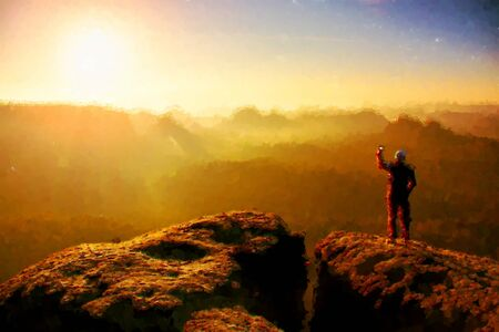 Watercolor paint. Paint effect.Man Takes photos with smart phone on the peak of rock empire. Dreamy landscape fogy