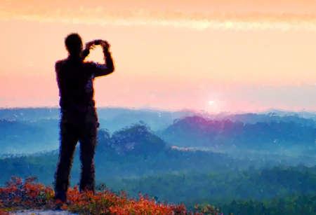 Watercolor paint. Paint effect.Hiker in sportswear on peak Takes photo of a misty valley Reklamní fotografie