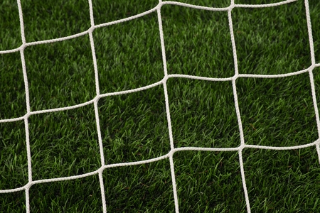 bended: Hang bended soccer nets, soccer football net. Grass on football playground in the background