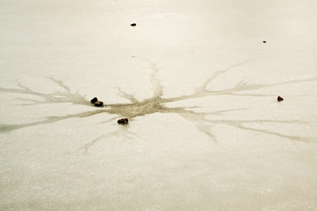 children pond: Cracks and hole in ice on pond, dark ice in hole and stone around. Children game. Stock Photo