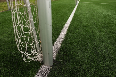 the game is over: Hang bended soccer nets, soccer football net. Grass on football playground in the background