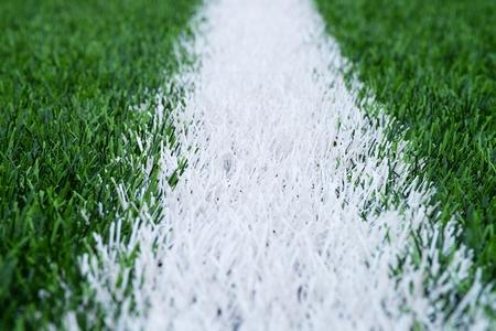 pasto sintetico: marcas de línea blanca pintada en el fondo verde del césped artificial. Invierno campo de fútbol con césped de plástico. Foto de archivo