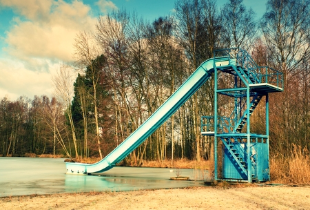 winter time: Old blue sliding track on lake beach, frozen watel level. Winter time at natural swimming resort