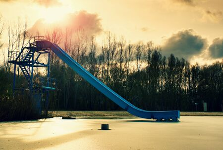 lake beach: Old blue sliding track on lake beach, frozen watel level. Winter time at natural swimming resort