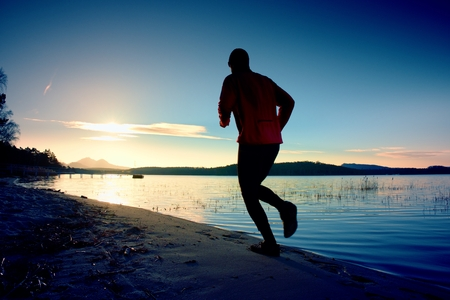 tall man: Tall man with pink windcheater and dark cap is running on sand at sunset Stock Photo