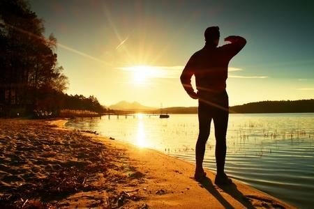 tall man: Tall man enjoying life. Sunset above island and wharf  at coastline. Warm colors and hues of the rising sun Stock Photo