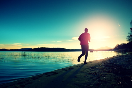fun activity: Silhouette of sport active man running and exercising on the beach at sunset. Stock Photo