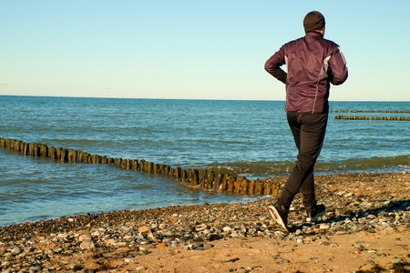 tall man: Silhouette of tall man in black running  and exercising on stony beach at breakwater. Vivid and strong vignetting effect
