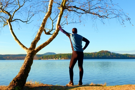 Silhouette of sport active adult man in running leggins and blue shirt at birch tree on  beach. Calm water, island and sunny day background.