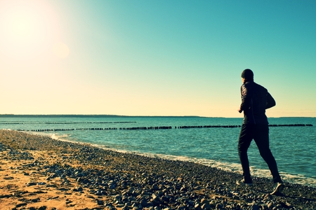 vignetting: Silhouette of tall man in black running  and exercising on stony beach at breakwater. Vivid and strong vignetting effect