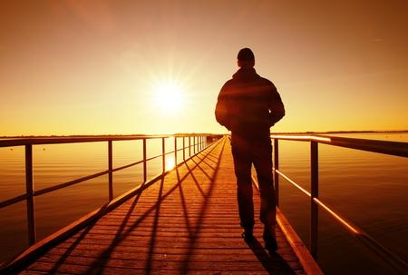 澄んだ空、滑らかな水位と日幻想的な朝に海抜埠頭建設男シルエット徒歩 写真素材