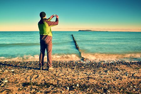 tall man: Tall man hold cellphone, take picture of autumn  sea scenery at breakwater.  Vivid and vignetting effect. Stock Photo