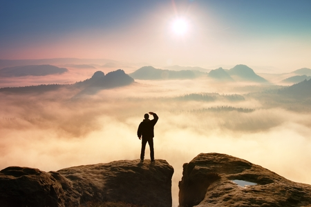 Kleurrijke mistige ochtend in de rotsen. Toerist in donkere kleding op rots imperium shadowing ogen met de hand in de lucht. Stockfoto