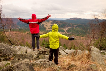 warm jacket: Boy in yellow and man in red warm jacket stand on a rock in a cold windy spring day. Active lifestyle, outdoor activities, hike in nature