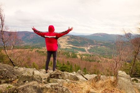 Man stand on a rock in a cold windy spring day. Active lifestyle, outdoor activities, hike in nature