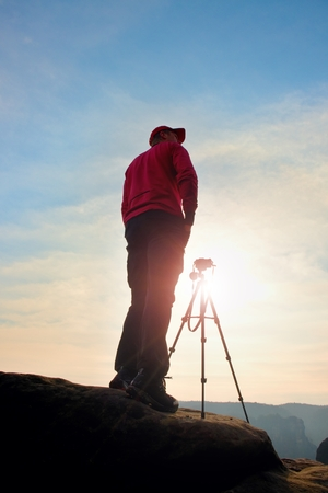stay beautiful: Photographer stay with tripod on cliff and thinking. Dreamy fogy landscape, orange misty sunrise in a beautiful valley below