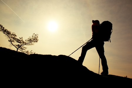 Tourist with sporty backpack and poles in hands stand on rock  watching up to hill for next step. Sunny spring daybreak in mountains.